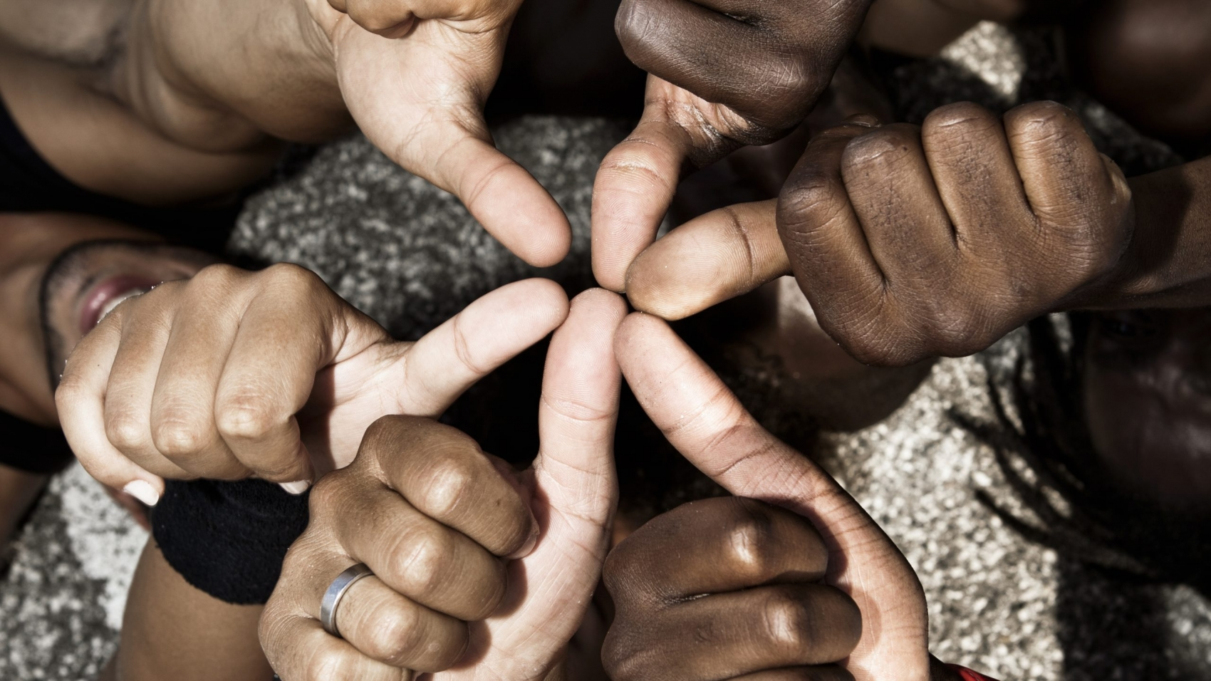 A group of mixed race people with hands doing thumbs up